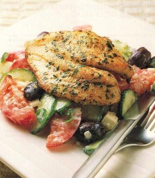 Grilled fish fillets on Greek salad